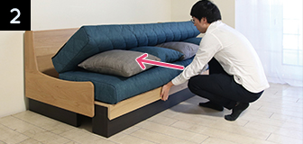 ソファの正面にかがみ、座面下のフレーム中央部分をつかんで止まるまで奥へ押し込みます。